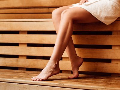 partial view of barefoot girl in towel in sauna